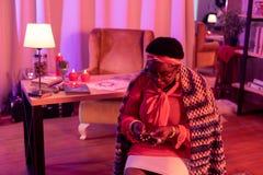 Amerykanin afrykańskiego pochodzenia tłuściuchny kabalista siedzi w wróżba salonie z dużymi pierścionkami obraz stock