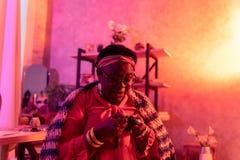 Amerykanin afrykańskiego pochodzenia tłuściuchny kabalista z dużymi pierścionkami pracuje w wróżba salonie zdjęcia royalty free
