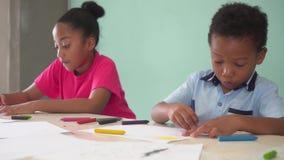 Amerykanin Afrykańskiego Pochodzenia żartuje uczenie dlaczego rysować z kredką na stole zbiory wideo