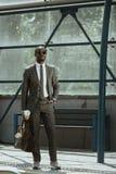 Amerykanin afrykańskiego pochodzenia biznesmen jest ubranym kostium z teczki i filiżanki pozycją na społeczeństwie obraz royalty free