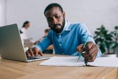 amerykanin afrykańskiego pochodzenia biznesmen pisze w podręczniku i używa laptop przy stołem i kolegami obrazy stock