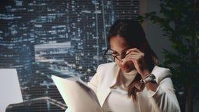 Amerykanin afrykańskiego pochodzenia biznesowa kobieta czyta dokument w eyeglasses zbiory wideo