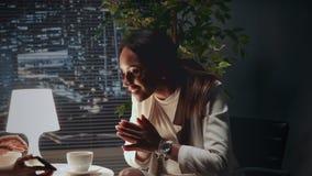 Amerykanin afrykańskiego pochodzenia biznesowa kobieta pokazuje podniecenie oglądać coś na smartphone zdjęcie wideo