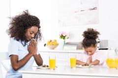 amerykanin afrykańskiego pochodzenia córki i matki modlenie przed śniadaniem fotografia royalty free