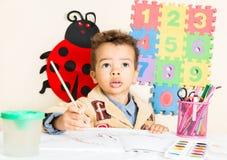 Amerykanin Afrykańskiego Pochodzenia chłopiec czarny rysunek z kolorowymi ołówkami w preschool przy stołem Obraz Royalty Free