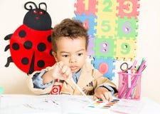 Amerykanin Afrykańskiego Pochodzenia chłopiec czarny rysunek z kolorowymi ołówkami w preschool a w dziecinu Zdjęcie Royalty Free