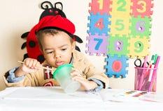Amerykanin Afrykańskiego Pochodzenia chłopiec czarny rysunek z kolorowymi ołówkami w preschool w dziecinu Zdjęcia Royalty Free