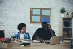 Amerykanin Afrykańskiego Pochodzenia chłopiec robi pracie domowej gdy ojciec fotografia royalty free