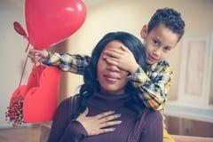Amerykanin Afrykańskiego Pochodzenia chłopiec trzyma jego matki zamykających oczy patrzeć Obrazy Stock