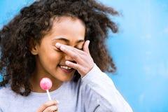 Amerykanin afrykańskiego pochodzenia dziewczyna outdoors je lizaka z kędzierzawym włosy Obrazy Stock