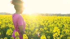 Amerykanin Afrykańskiego Pochodzenia dziewczyny nastolatka żeńska młoda kobieta biega butelkę woda w polu żółci kwiaty, jogging l zbiory