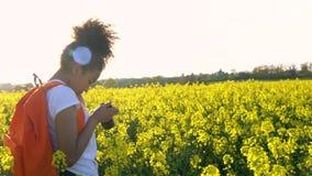 Amerykanin Afrykańskiego Pochodzenia dziewczyny nastolatka żeńska młoda kobieta z czerwonym plecakiem i kamerą bierze fotografię  zbiory
