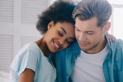 Amerykanin afrykańskiego pochodzenia dziewczyny obejmowania chłopak podczas gdy siedzący zdjęcia stock