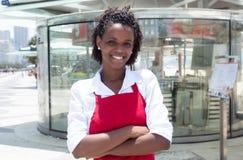 Amerykanin afrykańskiego pochodzenia kelnerka przed restauracją obrazy stock