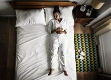 Amerykanin Afrykańskiego Pochodzenia kobieta na łóżkowy sypialny samotnym fotografia royalty free