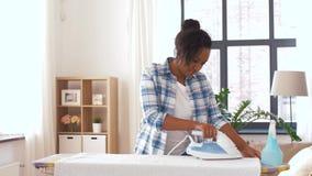 Amerykanin Afrykańskiego Pochodzenia kobieta odprasowywa łóżkową pościel w domu zdjęcie wideo