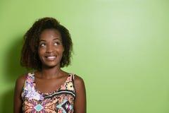 Amerykanin afrykańskiego pochodzenia kobieta patrzeje z ukosa zielona ściana fotografia stock