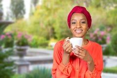 Amerykanin afrykańskiego pochodzenia kobieta pije herbaty od filiżanki lub kubka zdjęcie stock