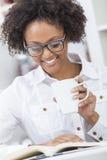 Amerykanin Afrykańskiego Pochodzenia kobieta Pije Kawową Czytelniczą książkę Zdjęcia Stock