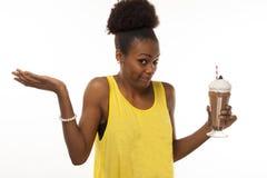 Amerykanin Afrykańskiego Pochodzenia kobieta próbuje robić zdrowym decyzjom o czekoladowym potrząśnięciu Fotografia Stock