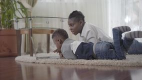 Amerykanin afrykańskiego pochodzenia kobieta pracuje na laptopu lying on the beach na dywanie i jej mały śliczny syn przychodzimy zbiory wideo