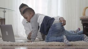 Amerykanin afrykańskiego pochodzenia kobieta pracuje na laptopu lying on the beach na dywanie i jej małym ślicznym synu przychodz zbiory
