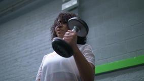 Amerykanin Afrykańskiego Pochodzenia kobieta pracuje z dumbbells w gym zbiory wideo