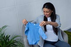 amerykanin afrykańskiego pochodzenia kobieta w ciąży trzyma błękitnego dziecka bodysuit podczas gdy siedzący fotografia royalty free