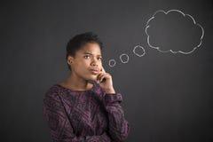 Amerykanin Afrykańskiego Pochodzenia kobieta z ręką na podbródka główkowania myśli chmurnieje na blackboard tle Zdjęcia Stock