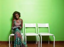 Amerykanin afrykańskiego pochodzenia kobiety czytelniczy magazyn w poczekalni docto zdjęcia royalty free