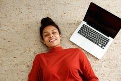 Amerykanin afrykańskiego pochodzenia kobiety lying on the beach na dywanie z laptopem zdjęcia royalty free