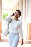 Amerykanin afrykańskiego pochodzenia kobiety odprowadzenie i opowiadać z telefonem komórkowym Zdjęcie Stock