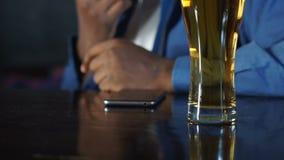 Amerykanin afrykańskiego pochodzenia mężczyzny obsiadanie w sportach karczemnych pijący piwnego i czekać na wezwanie zdjęcie wideo