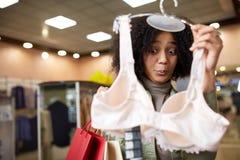 Amerykanin afrykańskiego pochodzenia mieszająca biegowa kobieta rozważa brassiere w sklepie Emocjonalna śmieszna czarna dziewczyn Obrazy Royalty Free
