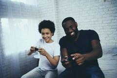 Amerykanin Afrykańskiego Pochodzenia ojciec z synem bawić się gra wideo zdjęcia royalty free