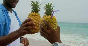 Amerykanin afrykańskiego pochodzenia para wznosi toast ananasowych soki na plaży 4k zbiory wideo