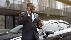 Amerykanin Afrykańskiego Pochodzenia pokazuje aprobaty mówi na telefonie, kierownik wnioskował tranzakcja zdjęcia royalty free