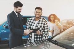 Amerykanin afrykańskiego pochodzenia rodzina przy przedstawicielstwem firmy samochodowej Sprzedawca daje papierom dla nowego samo obrazy stock