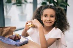 Amerykanin afrykańskiego pochodzenia uczennicy łasowania kanapka i ono uśmiecha się przy kamerą przy lunchem w szkole obraz royalty free