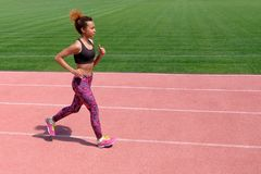 Amerykanin afrykańskiego pochodzenia w lato sportach Młoda seksowna sporty czarna dziewczyna biega wzdłuż różowej ścieżki stadium obraz royalty free