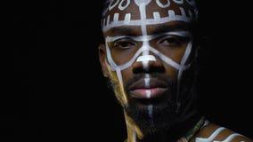 Amerykanin afrykańskiego pochodzenia z biel wzorami na jego ciele i kolii na jego szyja zwrotach kamera zbiory