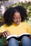 Amerykanin Afrykańskiego Pochodzenia kobiety czytelniczy outside w naturze zdjęcia stock