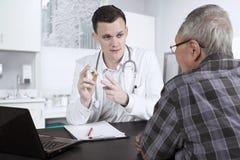 Amerykanin doktorska wyjaśnia medycyna dla jego pacjenta Obrazy Stock