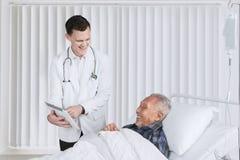 Amerykanin lekarka pokazuje pastylkę na starszym pacjencie obraz royalty free