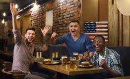 Amerykanin wachluje dopatrywanie mecz futbolowego i pić piwo fotografia royalty free