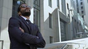 Amerykanina afrykańskiego pochodzenia biznesmen stoi blisko budynku biurowego, optymistycznie światopogląd zbiory