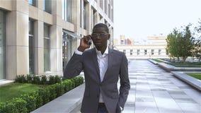 Amerykanina Afrykańskiego Pochodzenia biznesmena działanie: opowiadać na telefonie komórkowym Fotografia stylizujący spojrzenie,  zbiory wideo