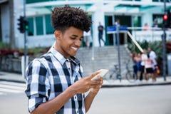 Amerykanina afrykańskiego pochodzenia dosłania młoda dorosła wiadomość z telefonem komórkowym Fotografia Stock