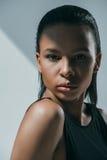 Amerykanina afrykańskiego pochodzenia elegancki elegancki model w czerni ubraniach patrzeje kamerę na popielatym Zdjęcie Royalty Free