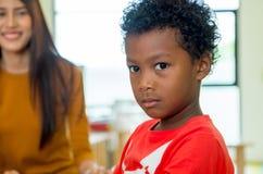 Amerykanina Afrykańskiego Pochodzenia pochodzenia etnicznego dzieciak z nauczycielem ono uśmiecha się przy backgroun Fotografia Stock
